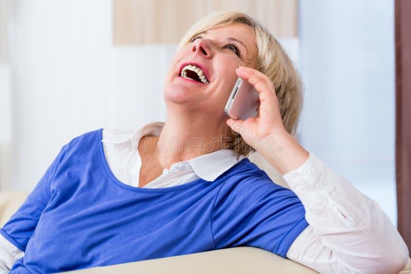 Starszy kobieta telefon siedzi na leżance w domu zdjęcia royalty free