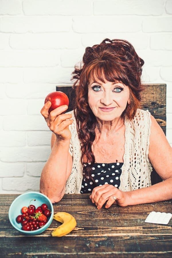 Starszy kobieta uśmiech z jabłkiem w ręce fotografia royalty free