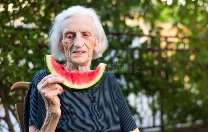 Starszy kobiety łasowania arbuz outdoors zdjęcie royalty free