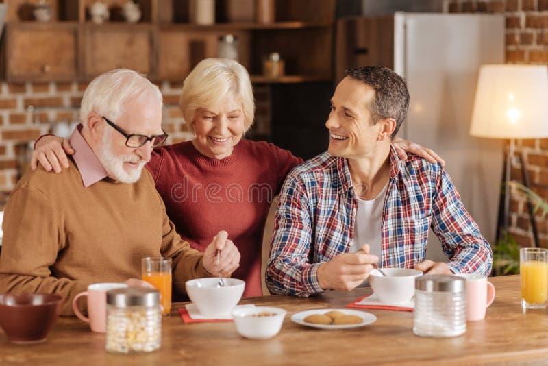 Starszy kobiety dopatrywania mąż i syn jemy oatmeal zdjęcia royalty free