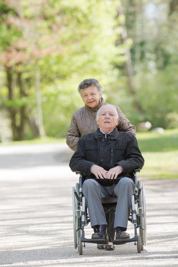 Starszy kobiety dosunięcia mężczyzna w wózku inwalidzkim zdjęcia royalty free