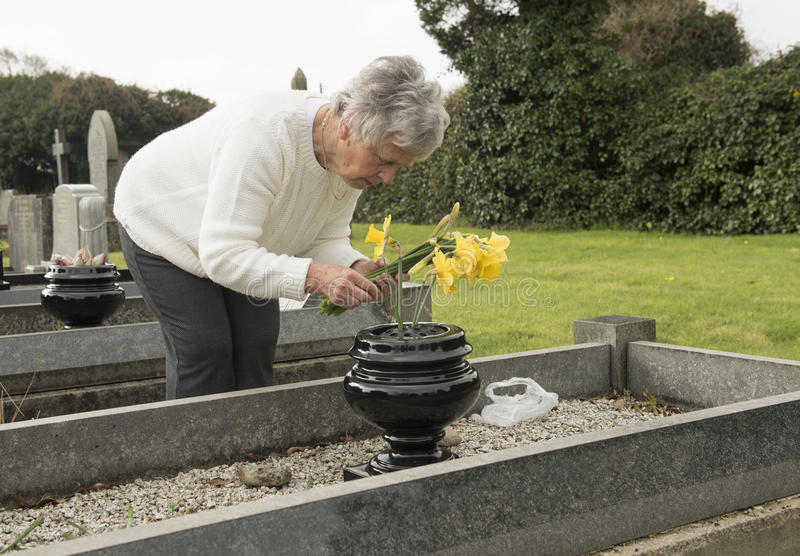 Starszy kobiety kładzenie kwitnie na grób fotografia royalty free
