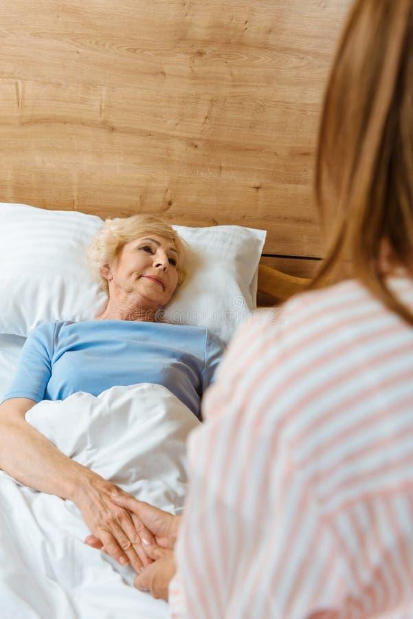 Starszy kobiety lying on the beach w łóżka szpitalnego i mienia ręce młody córki obsiadanie zdjęcie stock