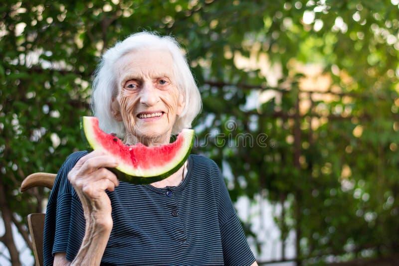 Starszy kobiety mienia arbuza plasterek w podwórku zdjęcie stock