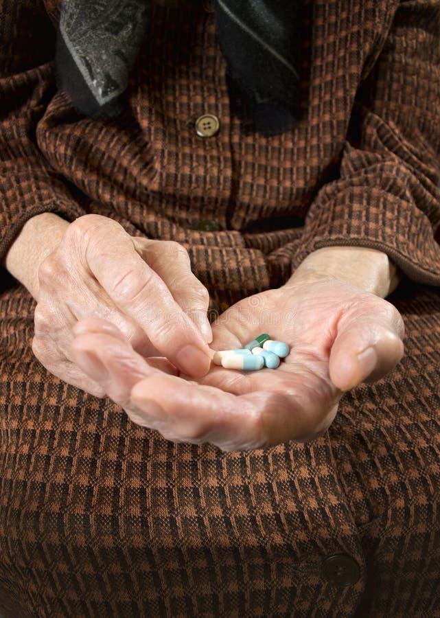 Starszy kobiety mienie dobierał kapsuły w jej rękach. obrazy stock