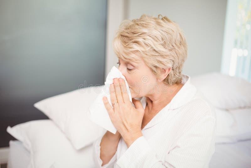 Starszy kobiety nakrycia nos podczas gdy kichający w domu zdjęcia royalty free