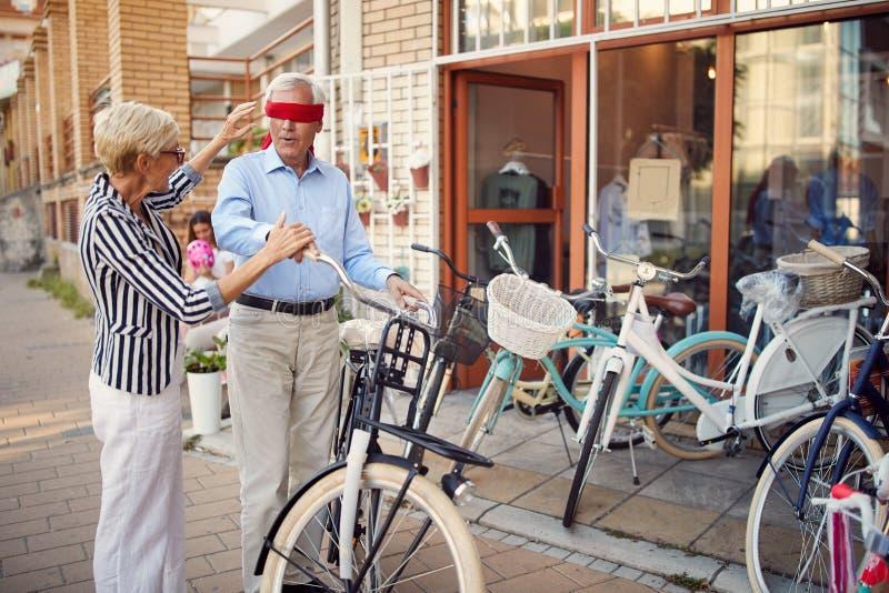 Starszy kobiety nakrycia oczy starszy mężczyzna dla niespodzianki z prezenta bicyklem obraz royalty free
