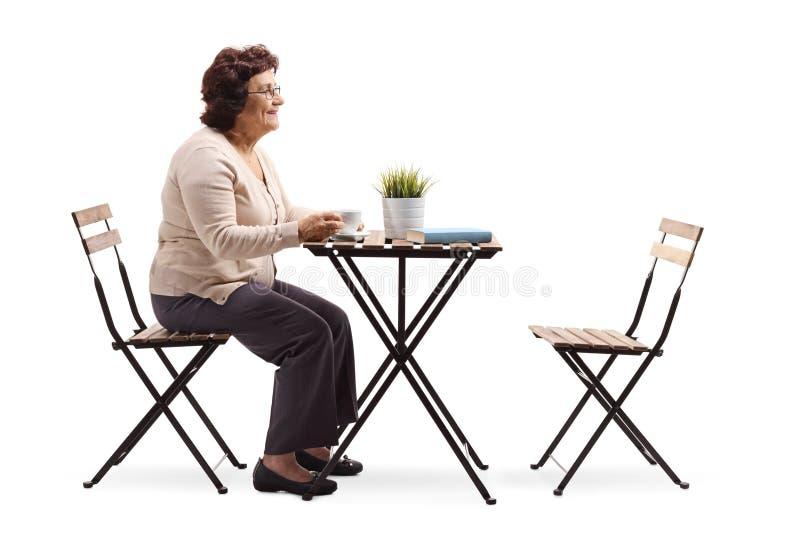 Starszy kobiety obsiadanie przy stołową pije kawą fotografia royalty free