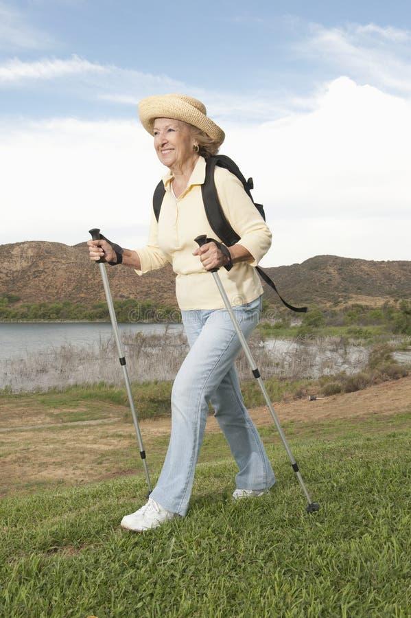 Starszy kobiety odprowadzenie Z Wycieczkować słupy fotografia stock