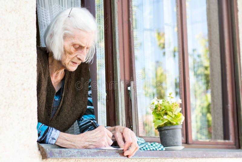Starszy kobiety podpisywania emerytura czek w domu zdjęcie stock