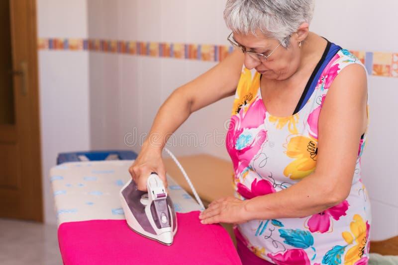 Starszy kobiety prasowanie odziewa obraz royalty free