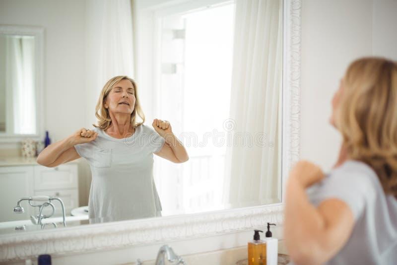 Starszy kobiety rozciąganie przed lustrem zdjęcia royalty free