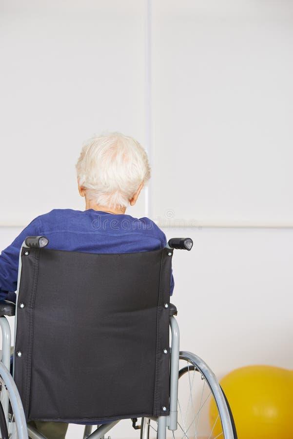 Starszy kobiety siedzieć osamotniony w wózku inwalidzkim obrazy stock
