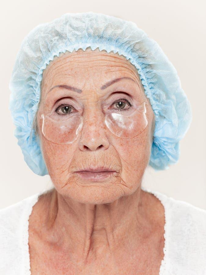 Starszy kobiety studio odizolowywający na biel ściany piękna pojęciu patrzeje kamerę robi maskom pod oczami obrazy royalty free