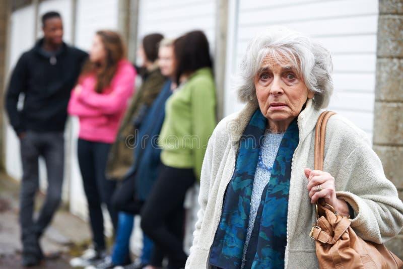 Starszy kobiety uczucie Onieśmielający grupą młodzi ludzie obraz stock