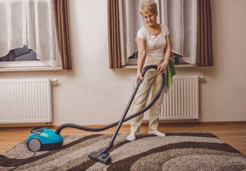 Starszy kobiety vacuuming zdjęcie stock