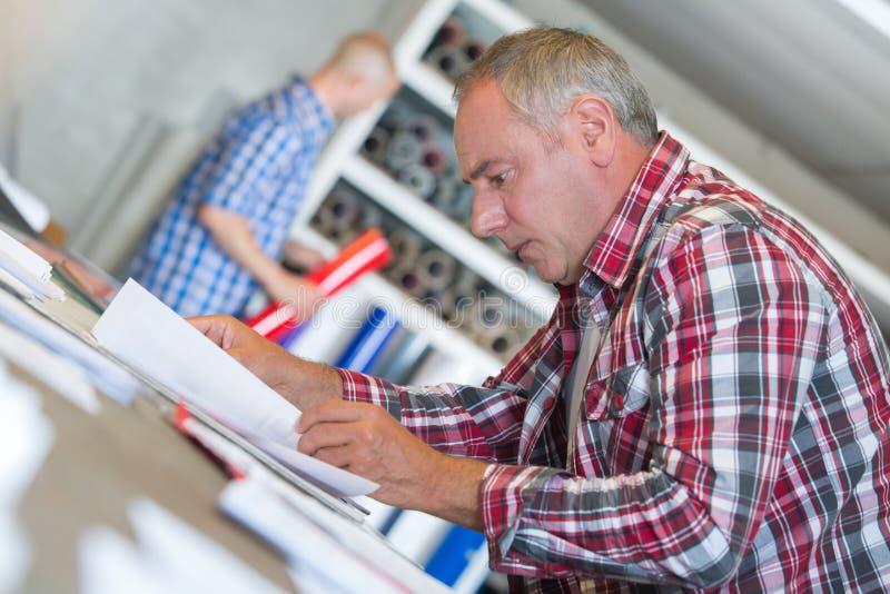 Starszy kontrahent przy biurkiem robi papierkowej robocie obraz royalty free