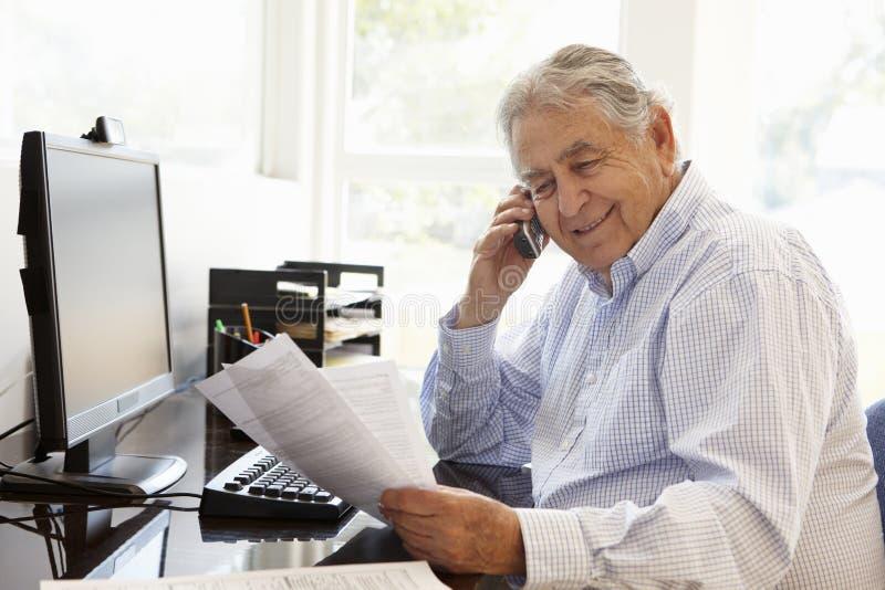 Starszy Latynoski mężczyzna pracuje na komputerze w domu obrazy stock