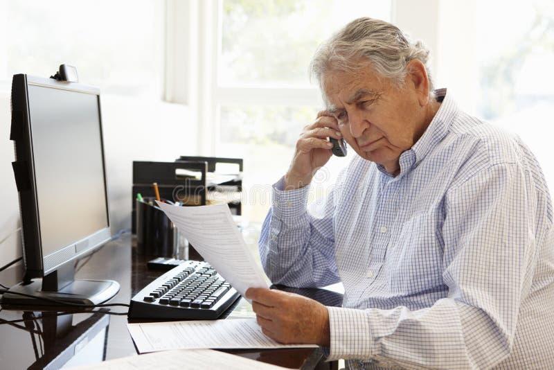 Starszy Latynoski mężczyzna pracuje na komputerze w domu fotografia stock