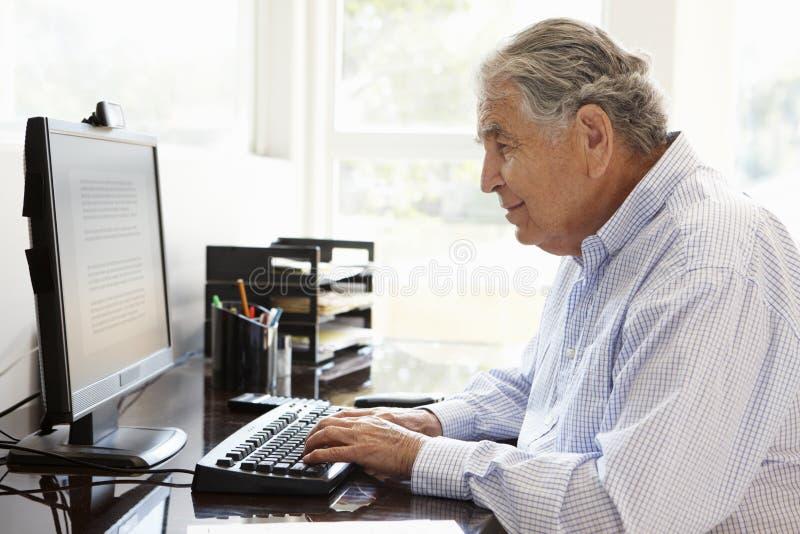 Starszy Latynoski mężczyzna pracuje na komputerze w domu obraz royalty free