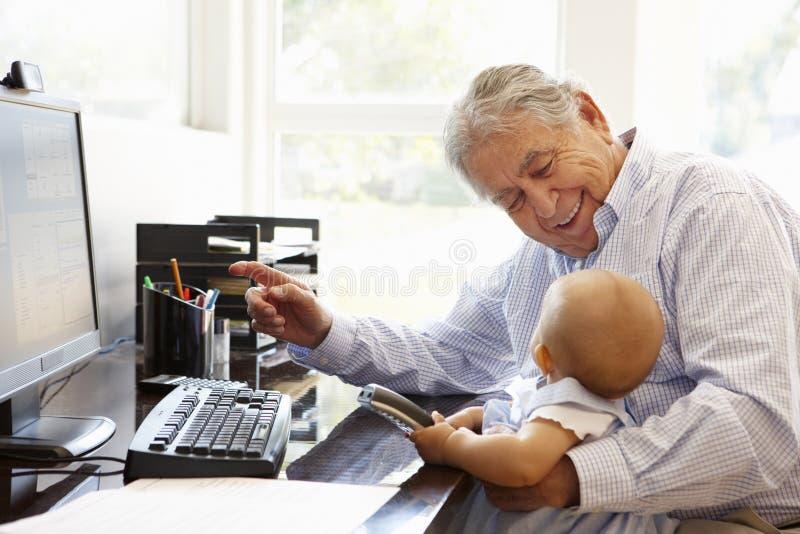 Starszy Latynoski mężczyzna z komputerem i dzieckiem obrazy stock
