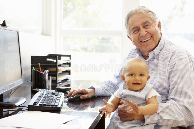 Starszy Latynoski mężczyzna z komputerem i dzieckiem zdjęcia stock
