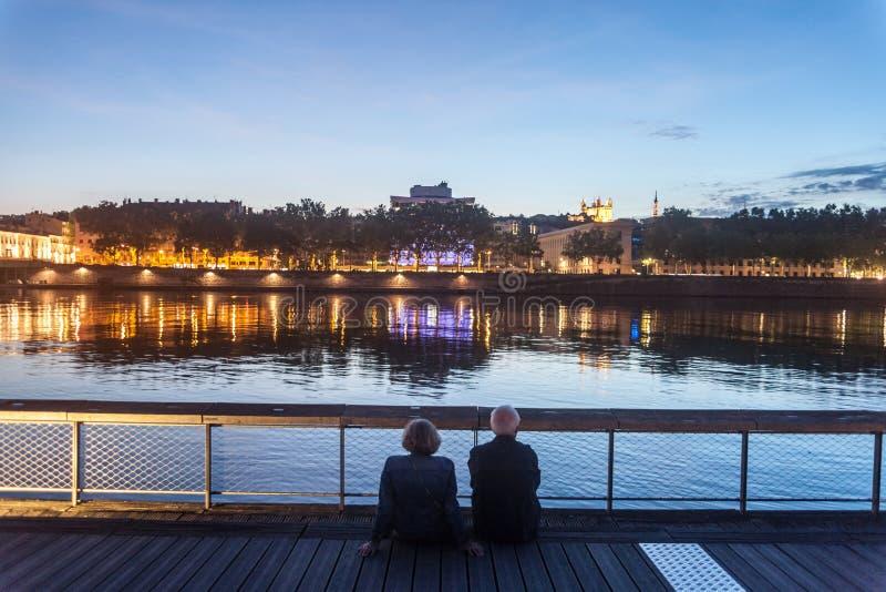 Starszy ludzie i stara para kochankowie, siedzi na quays riverbank Rhone podziwia rzekę podczas wieczór zdjęcie royalty free