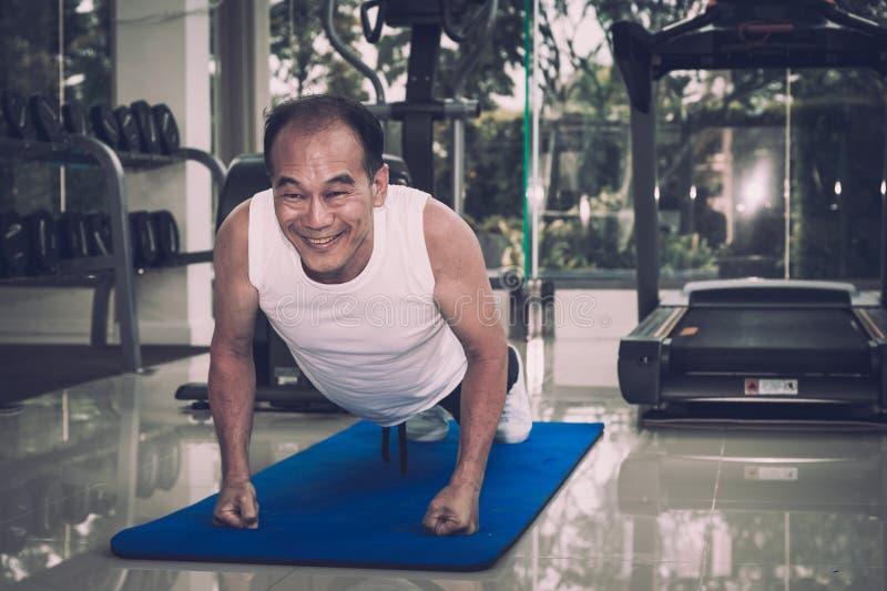 Starszy mężczyzna ćwiczy pcha ups w sprawności fizycznej centrum, robić obrazy royalty free