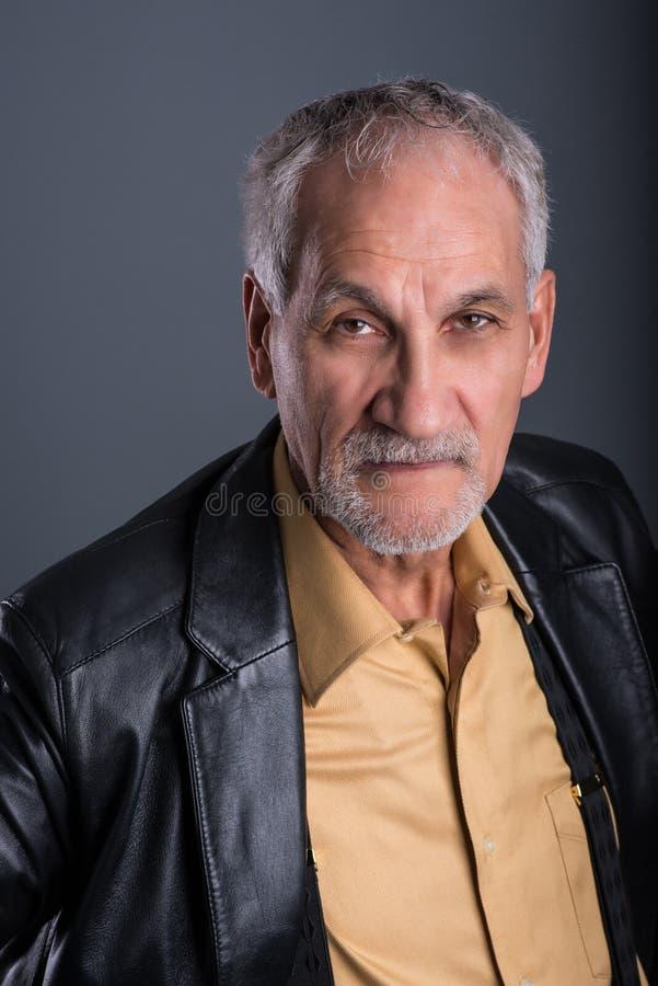 Starszy mężczyzna bardzo baczny z jego oczami skupia się na kamerze obrazy stock