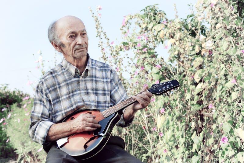 Starszy mężczyzna bawić się mandolinę fotografia stock