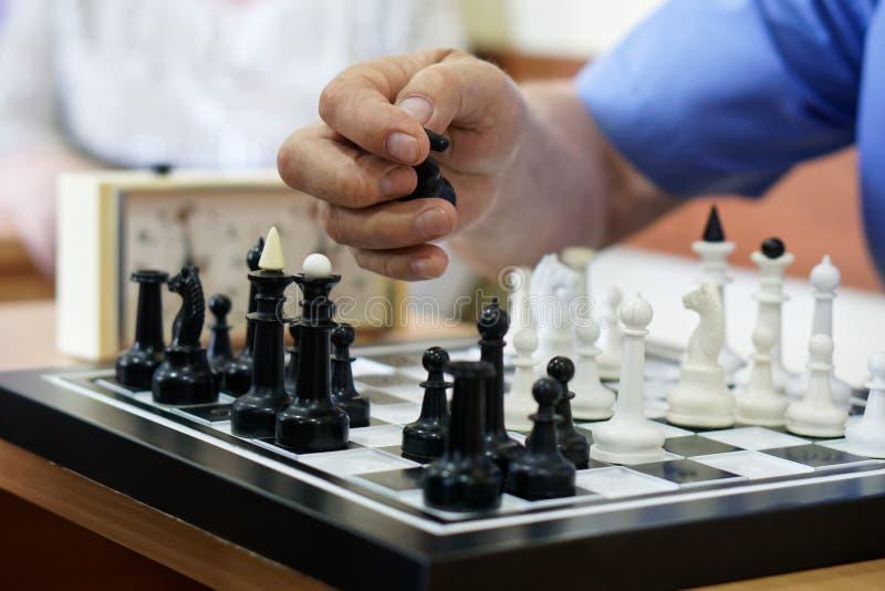 Starszy mężczyzna bawić się szachowego i bierze postać wróg fotografia royalty free