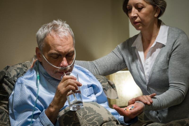 Starszy mężczyzna bierze lekarstwo z wodą fotografia stock