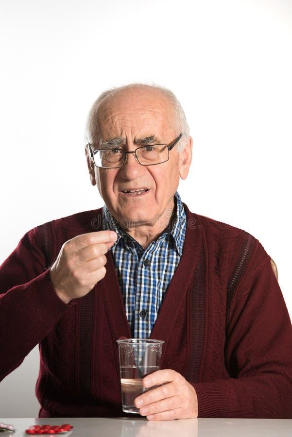 Starszy mężczyzna bierze pigułki fotografia stock