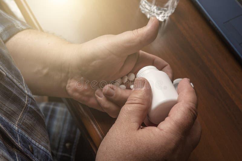 Starszy mężczyzna bierze pigułki, lekarstwo leki na ręce od butelki lub pastylki w domu lub fotografia royalty free