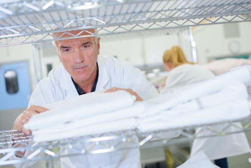 Starszy mężczyzna broguje czystą pralnię na półce zdjęcia stock