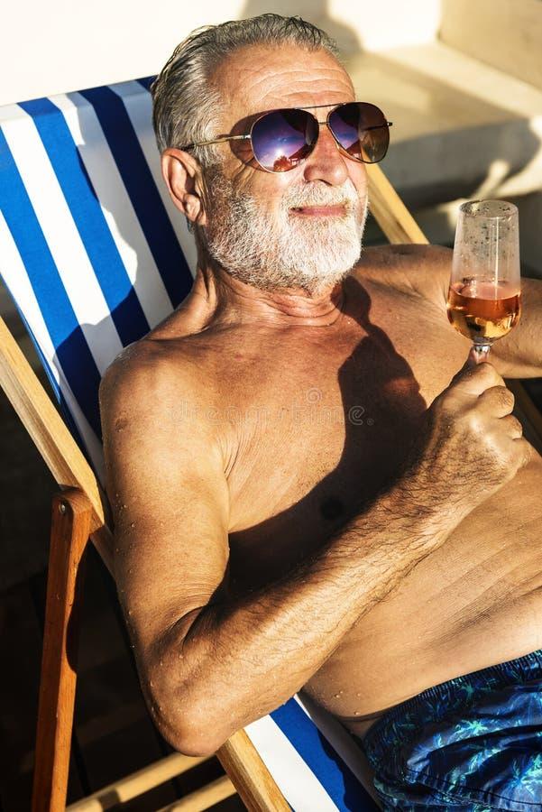 Starszy mężczyzna chłodzi wino na pokładu krześle i pije zdjęcie stock