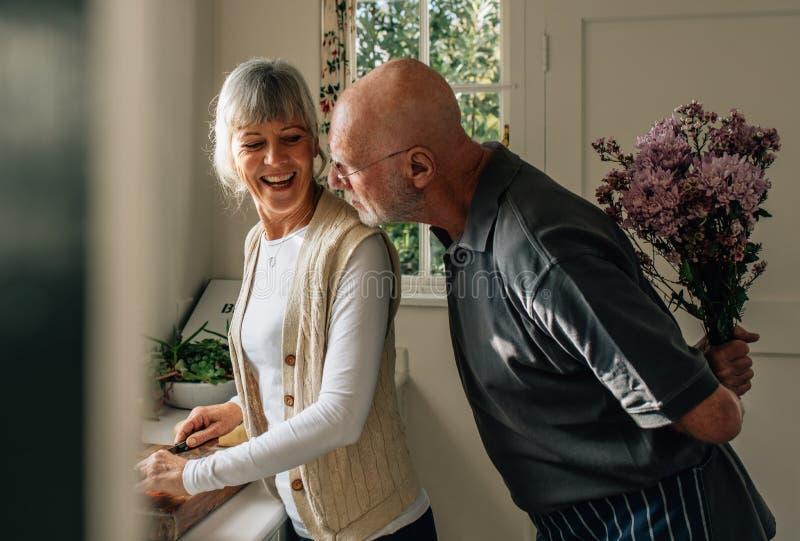 Starszy mężczyzna chuje wiązkę kwiaty za on zaskakiwać jego żony Kobiet tnący warzywa w kuchni podczas gdy jej mąż obrazy stock