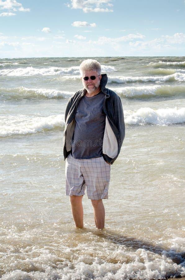 Starszy mężczyzna cieszy się emerytura przy plażą obraz royalty free