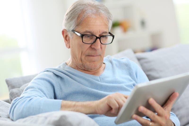 Starszy mężczyzna czyta cyfrową gazetę zdjęcia stock