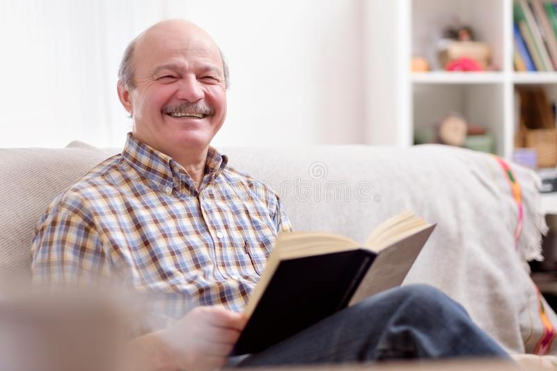Starszy mężczyzna czyta książkę na jego kanapie obraz stock