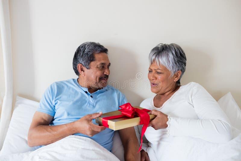 Starszy mężczyzna daje niespodzianka prezentowi starsza kobieta obraz royalty free