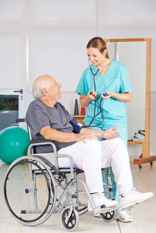 Starszy mężczyzna dostaje ciśnienie krwi pomiar obrazy royalty free