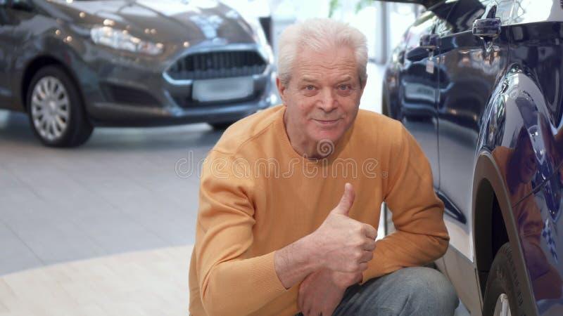 Starszy mężczyzna egzamininuje samochodowego koło przy przedstawicielstwem handlowym obrazy stock