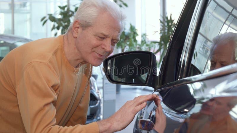 Starszy mężczyzna egzamininuje samochodu skrzydło przy przedstawicielstwem handlowym obraz stock