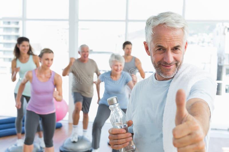 Starszy mężczyzna gestykuluje aprobaty z ludźmi ćwiczy w sprawności fizycznej studiu fotografia royalty free