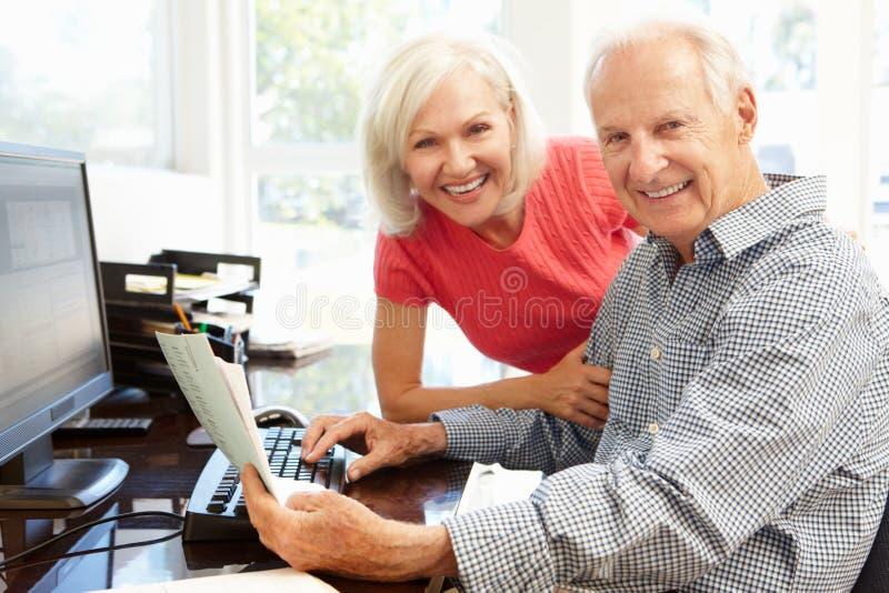 Starszy mężczyzna i córka używa komputer w domu obraz stock