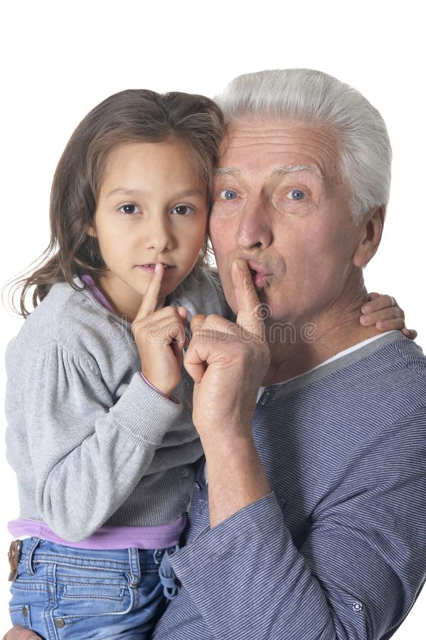 Starszy mężczyzna i mała dziewczynka gestykuluje ciszę z palcem na wargach na białym tle fotografia royalty free