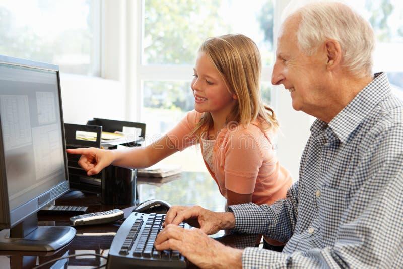 Starszy mężczyzna i wnuczka używa komputer obrazy royalty free