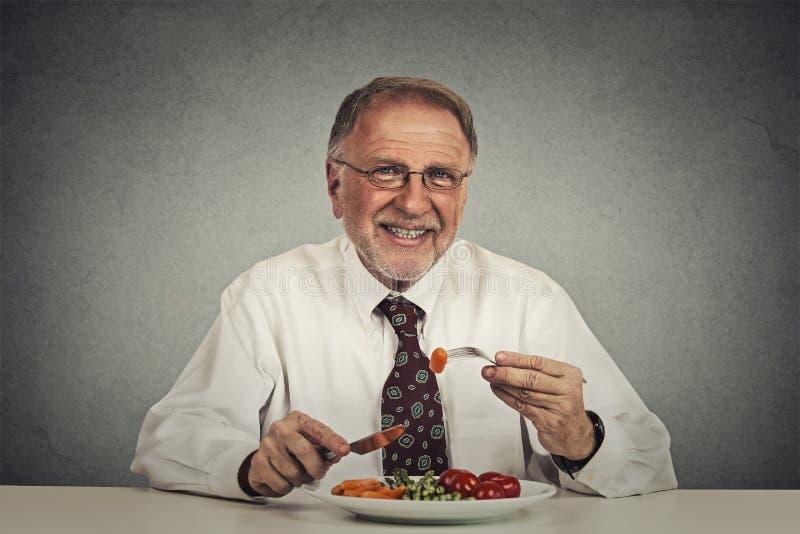 Starszy mężczyzna je świeżego warzywa sałatki zdjęcie royalty free