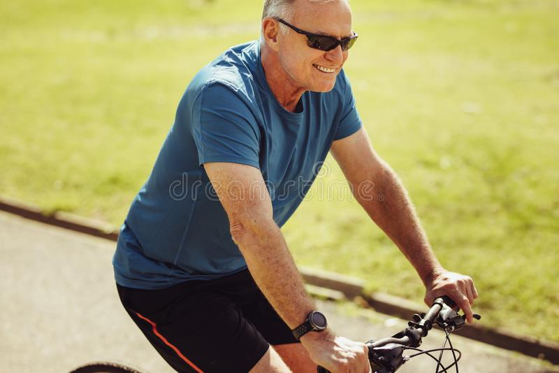 Starszy mężczyzna jedzie bicykl dla sprawności fizycznej fotografia stock